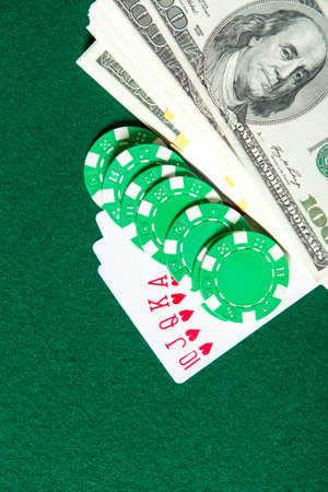 risky: Royal Flush poker card sequence with green chips and money on a green table. Risky entertainment of gambling Stock Photo