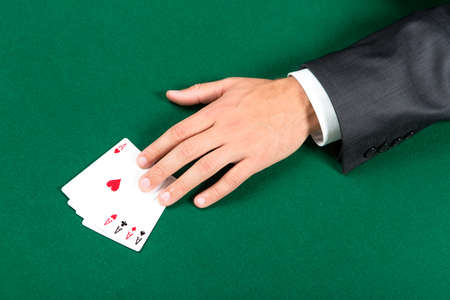 gambler: Hand with aces on the green table. Challenge to the casino