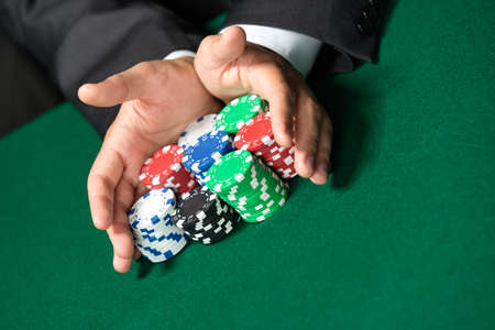 risky: Gambler stakes all in pushing his poker chips forward. Risky entertainment of gambling Stock Photo