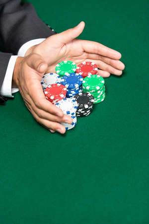 risky: Poker player going all in pushing his chips forward. Risky entertainment of gambling
