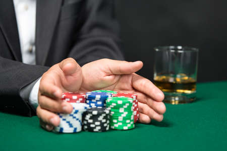 Poker player going all in pushing his poker chips forward. Risky entertainment of gambling photo