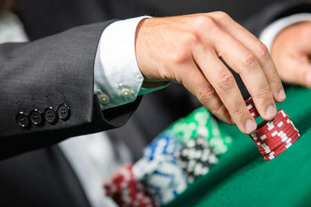 Gambler stakes the pile of chips. Risky entertainment of gambling photo