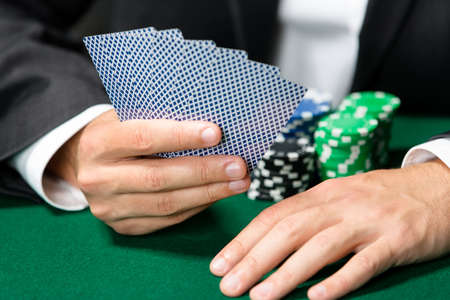 Gambler playing poker cards with chips on the table. Addiction to the gambling Stock Photo - 17822543
