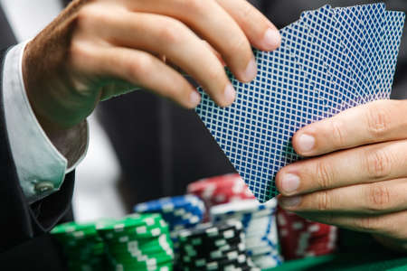 Gambler playing poker cards with poker chips on the poker table. Risky entertainment of gambling Stock Photo - 17822468