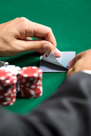 Gambler checking his cards. Risky entertainment of gambling photo