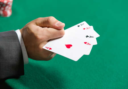 Gambler shows poker cards 4 aces. Addiction to the gambling photo