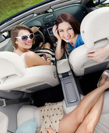 Top view of happy women with sunglasses sitting in the car photo