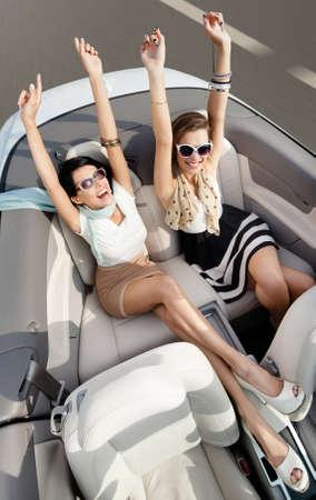 cabrio: Bovenaanzicht van gelukkige vrouwen in zonnebril met hun handen omhoog zitten in de cabriolet