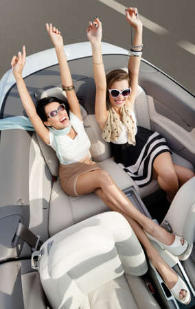 convertible: Top view of happy women in sunglasses with their hands up sit in the cabriolet Stock Photo