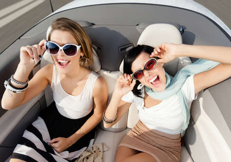 Top view of happy women with sunglasses sitting in the cabriolet photo