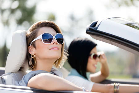 street shot: Close up of girls wearing sunglasses in the white car. Little holiday trip of friends
