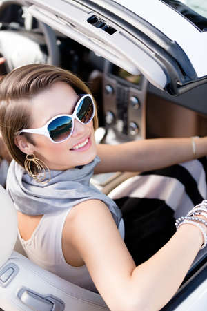 Pretty woman wearing sunglasses with white rim turns back sitting in the car photo