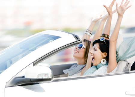manejando: Amigas conducci�n descapotable con las manos en alto y la diversi�n en las vacaciones
