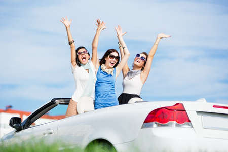 Group of girls stands in the automobile with hands up. Happy journey of joyful teenagers photo
