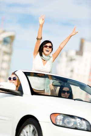 vertical format: Lovely teenager with her hands up in the car with friends. Girls ride somewhere on vacation Stock Photo