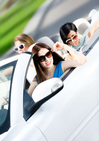 Group of happy teenagers driving the car. Adorable car trip on vacation photo