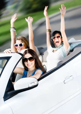 Group of happy teenagers driving the cabriolet. Adorable cabriolet trip on vacation photo