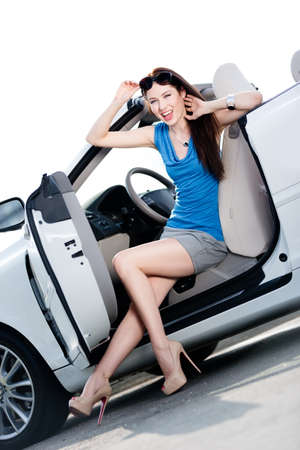 Pretty woman in sunglasses sits in the car with door opened photo