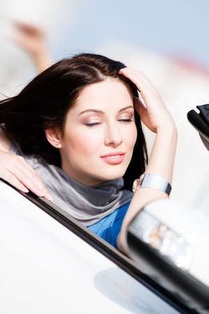 Close up of smiley woman with her eyes shut in the car photo