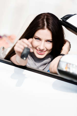 Girl in the cabriolet shows car key. Buying car and getting the freedom photo