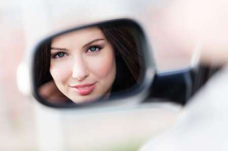 Reflection of pretty woman in the side-view mirror of the car that she took to have a little trip Stock Photo - 17932971
