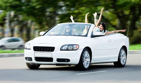 aandrijvingen: Gelukkig meisjes in de witte auto met uitgestrekte armen. Rijden en plezier tieners