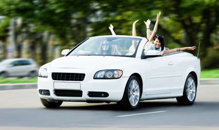 street shot: Happy girls in the white car with arms outstretched. Driving and having fun teenagers