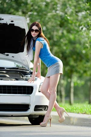 Woman repairing the broken car on the highway. Girl stands near opened hood of the car after an accident photo