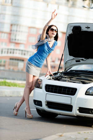 Woman thumbing a lift near the opened bonnet of the broken car and waiting for assistance photo