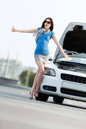 street shots: Woman hitchhiking near the opened bonnet of the broken car and waiting for assistance Stock Photo