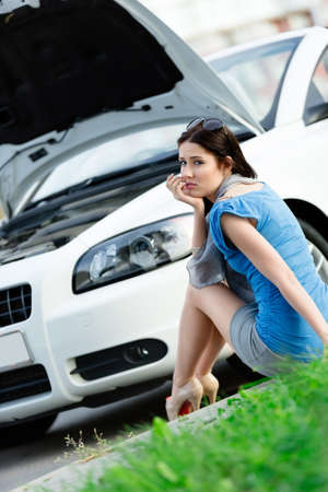 Woman sits on the grass near her broken car with the opened bonnet waiting for assistance photo