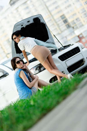 Two pretty girls try to repair the broken car on the highway photo