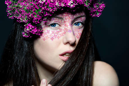 Portrait of young beautiful fresh girl with stylish make-up and pink flowers photo