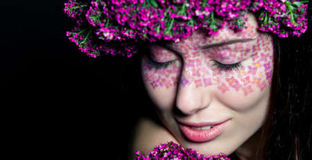 Close up portrait of model with flowered wreath and fashion make-up with eyes closed photo