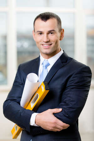 elevation meter: Engineer wearing suit with blue tie hands blueprint and level Stock Photo