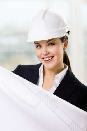 Female engineer in white hard hat hands sketch. Concept of successful construction photo