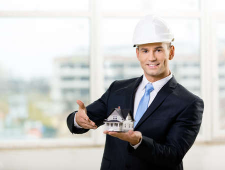 Engineer in white hard hat pointing at small model house. Concept of real estate photo