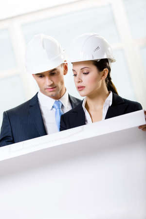 architecting: Two engineers looking at the blueprint and discuss their cooperation Stock Photo