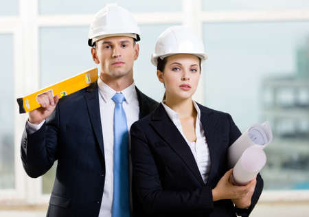 Two contractors in white hard hats keeping level and blueprints. Concept of successful construction photo