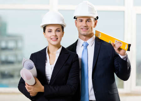elevation meter: Two engineers in white hard hats keeping level and blueprints. Concept of successful construction