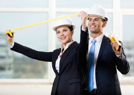 Two engineers in white hard hats keeping level and tape measure. Concept of successful construction photo