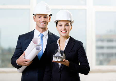 Two contractors in white hard hats keeping blueprints and model house Stock Photo - 17824552