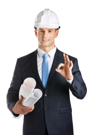 architecting: Engineer in hard hat hands blueprints and gestures Okay, isolated on white. Concept of successful construction Stock Photo