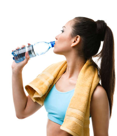 Athletic woman with yellow towel on the shoulders drinks water from the bottle, isolated on white photo