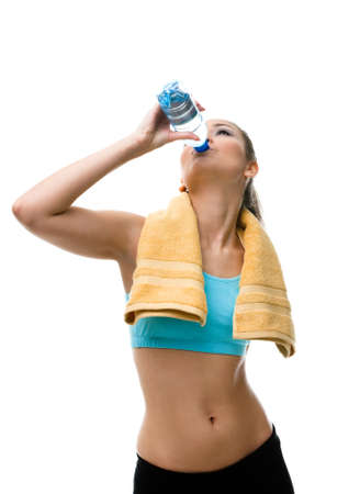 Sportive woman with yellow towel on the shoulders drinks water from the bottle, isolated on white Stock Photo - 17824286