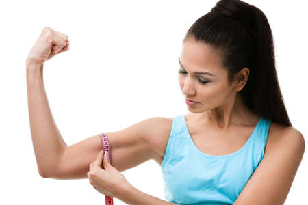 female muscle: Sportive woman measures her bicep with   measuring tape, isolated on white Stock Photo