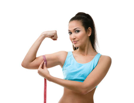 tricep: Sporty woman measures her bicep with   measuring tape, isolated on white