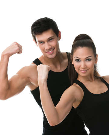 Two sportive people in black sportswear showing their biceps, isolated photo