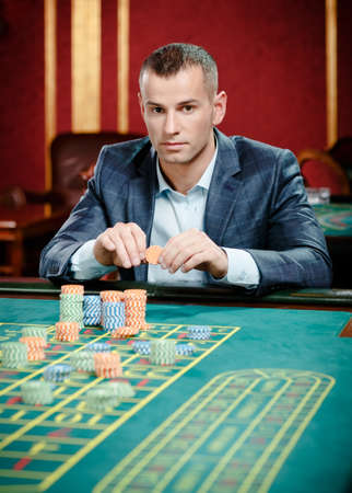Gambler playing roulette at the casino table. Risky entertainment of gambling photo