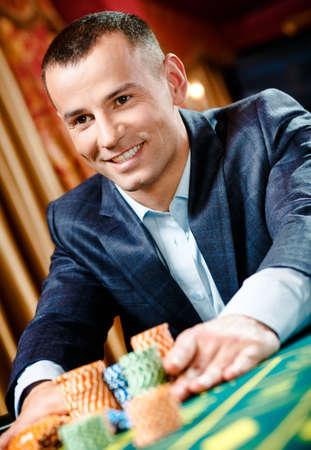 ruleta de casino: Cierre de estacas jugador jugando a la ruleta en el casino. Risky entretenimiento de juegos de azar